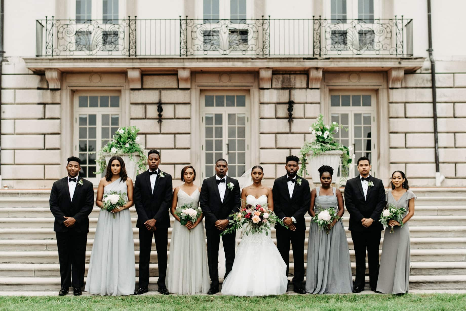 bride and groom pose with their wedding party in tuxedos and pale blue grey