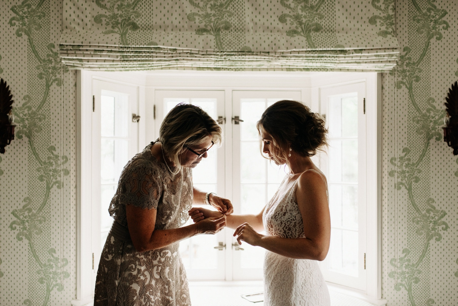 mother of the bride helps her daughter put on a bracelet