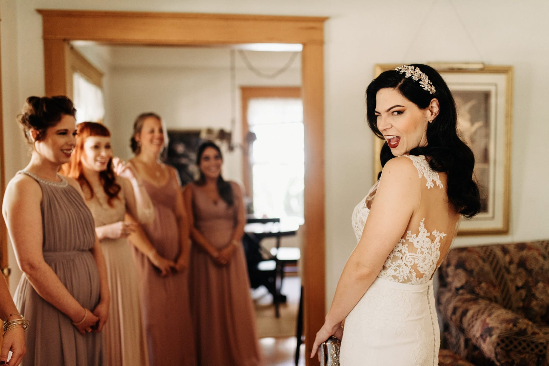bride revealing herself to her bridesmaids