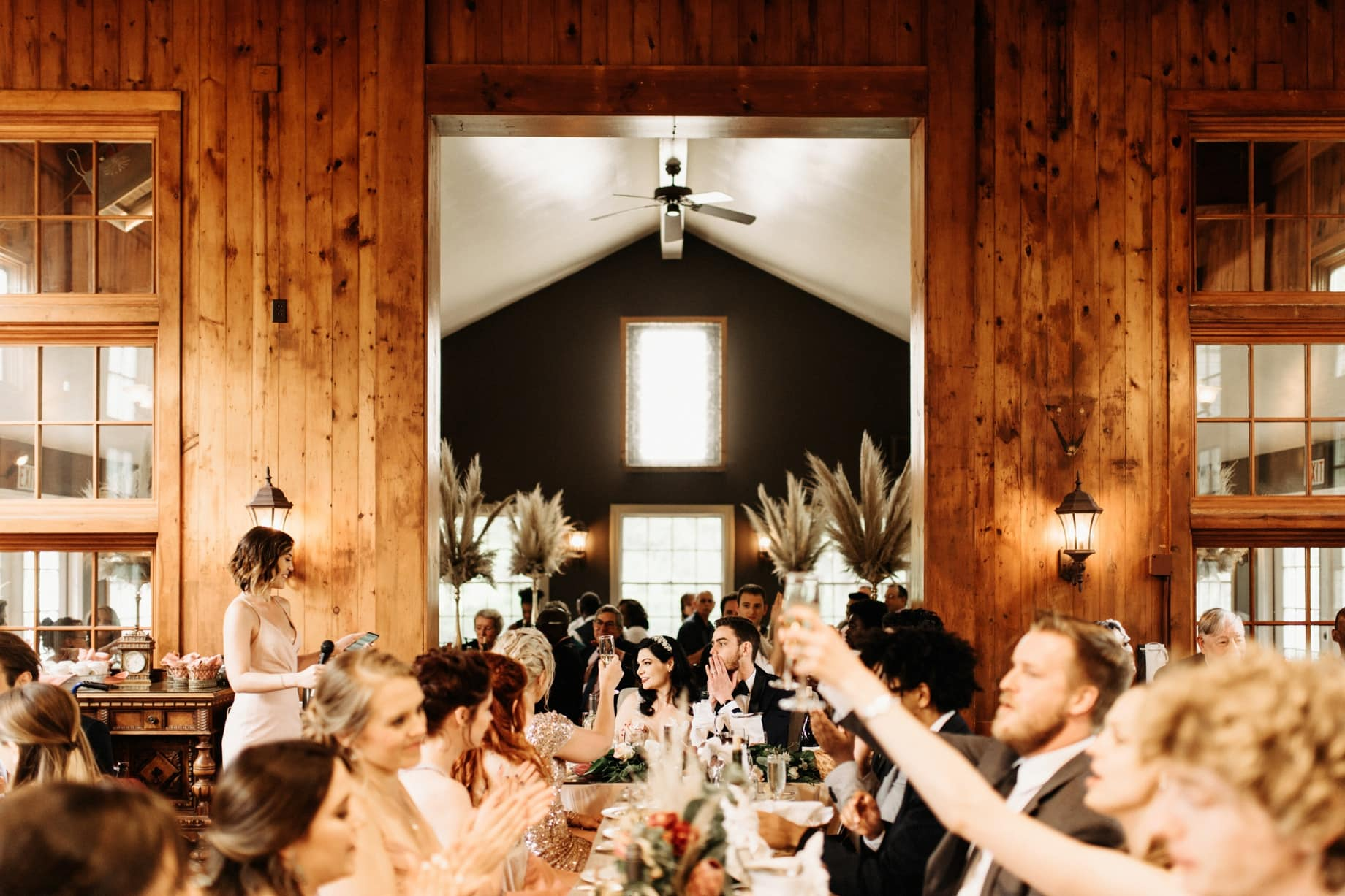 guests raise a glass during toasts at a wellers carriage house wedding