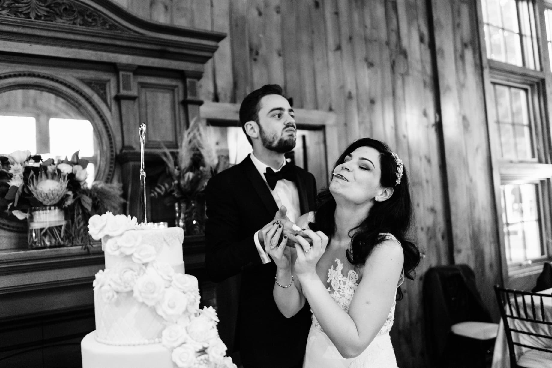 bride and groom taking a first bite of their wedding cake