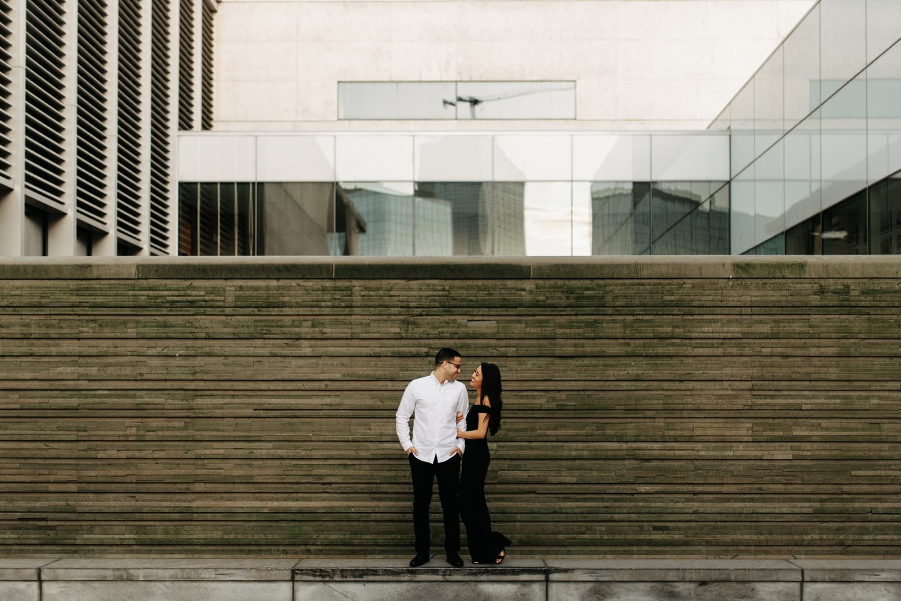 a couple poses for engagement photos at the grand rapids art museum