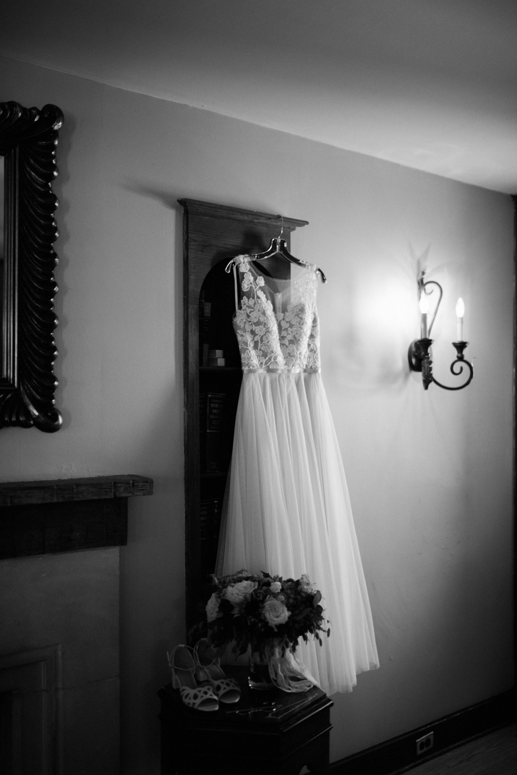 Black and white photo of a wedding dress hanging