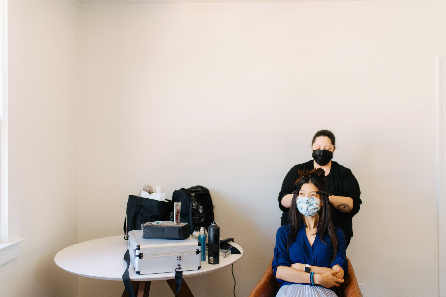 a bride gets ready while wearing a face mask by photojournalistic Detroit wedding photographer Heather Jowett