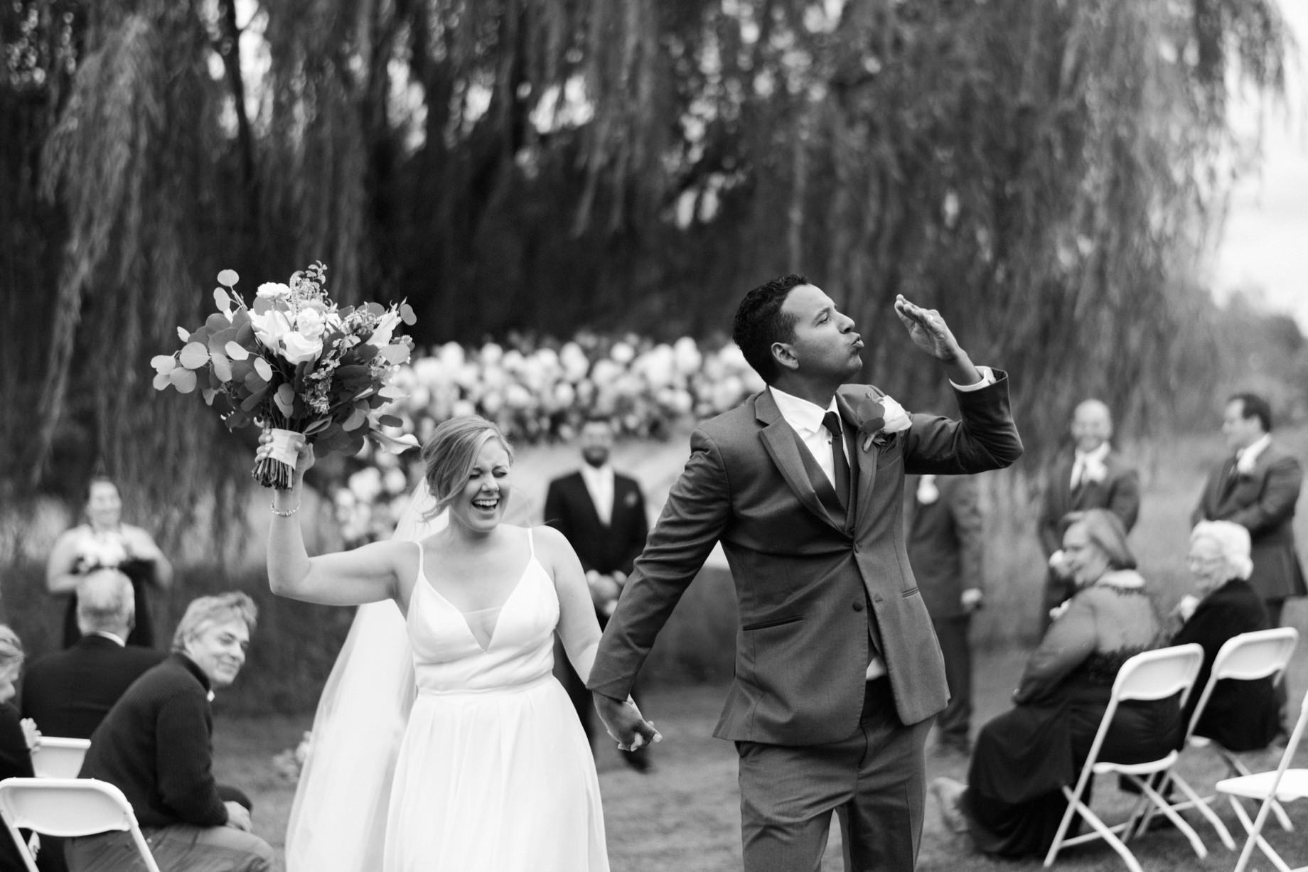 a groom blows a kiss after his wedding ceremony