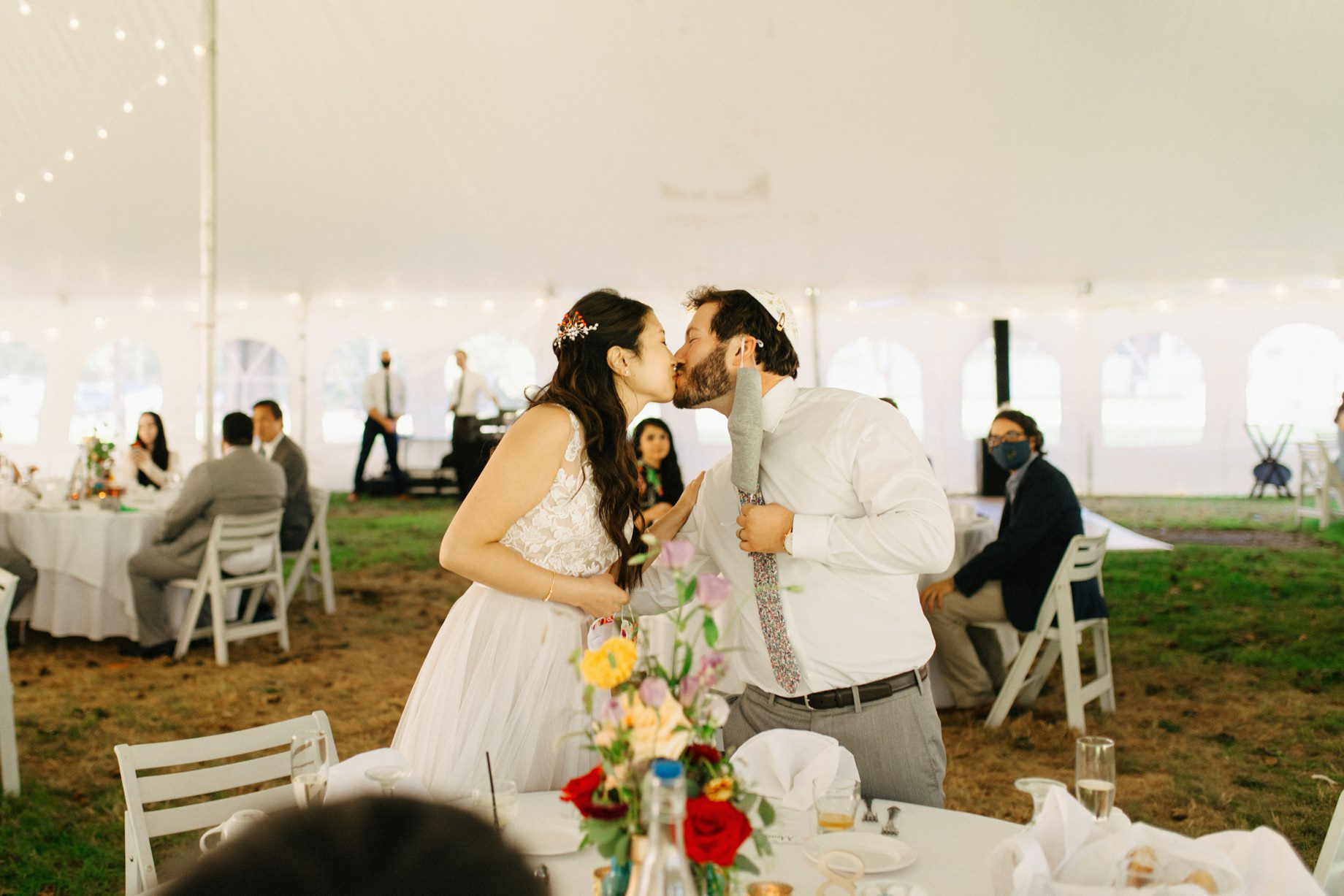 a couple shares a kiss during their wedding reception
