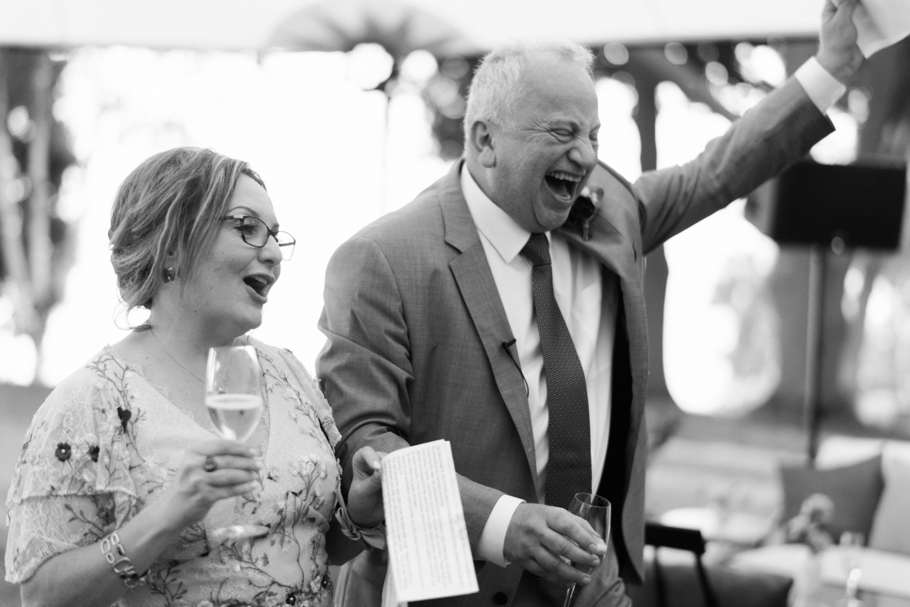 parents of the groom enthusiastically toast their son
