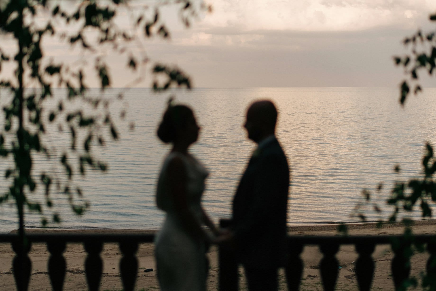 bride and groom silhouetted against lake huron in lexington michigan