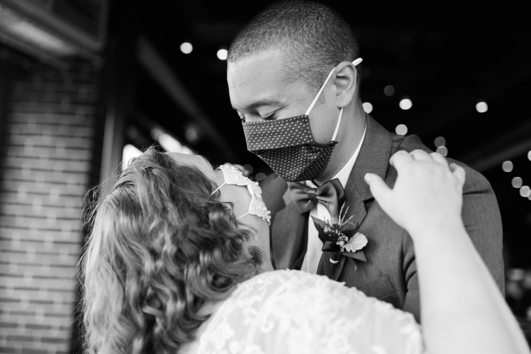 bride and groom dance with masks on during their covid wedding
