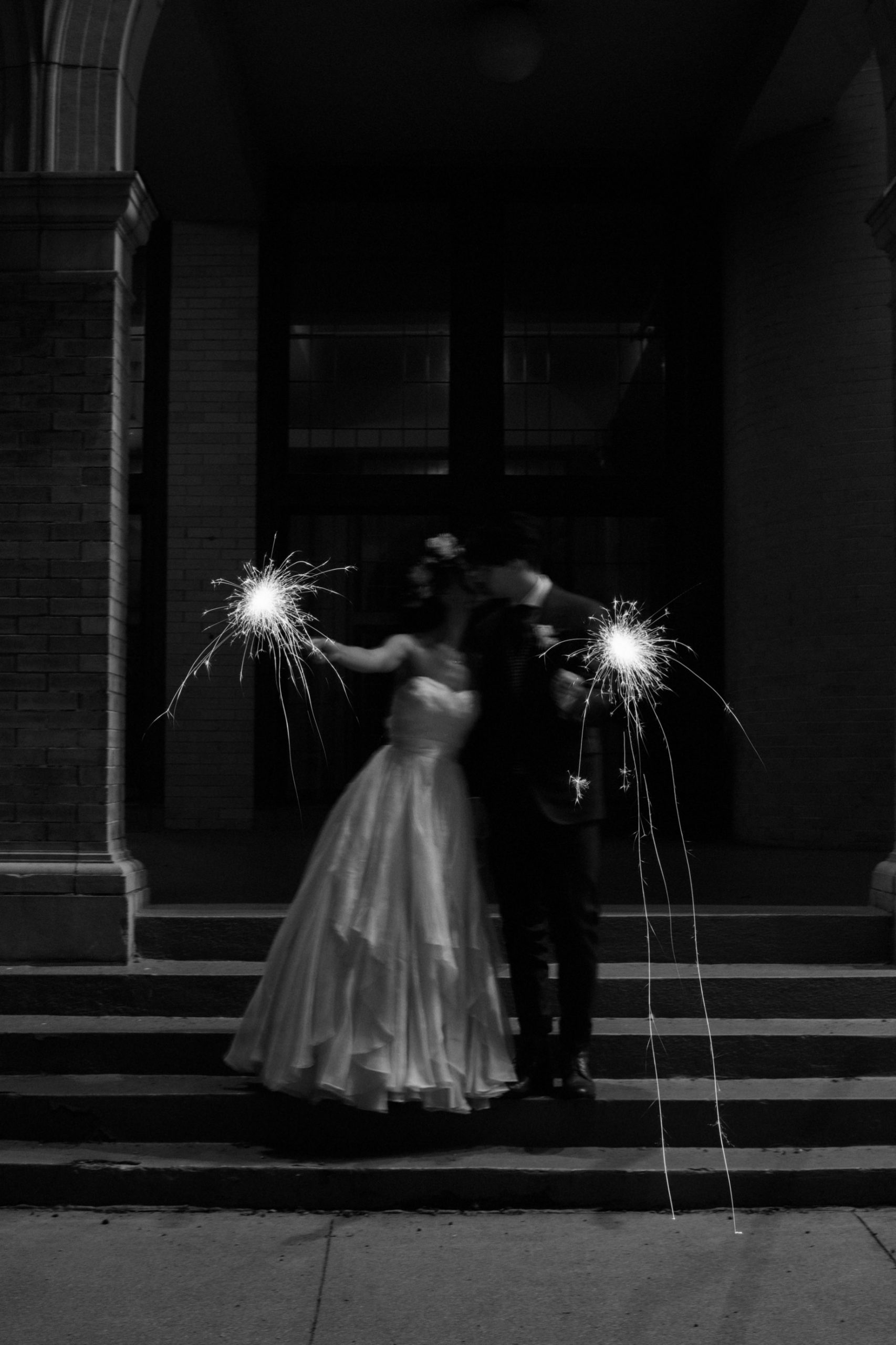 a couple kisses while holding sparklers