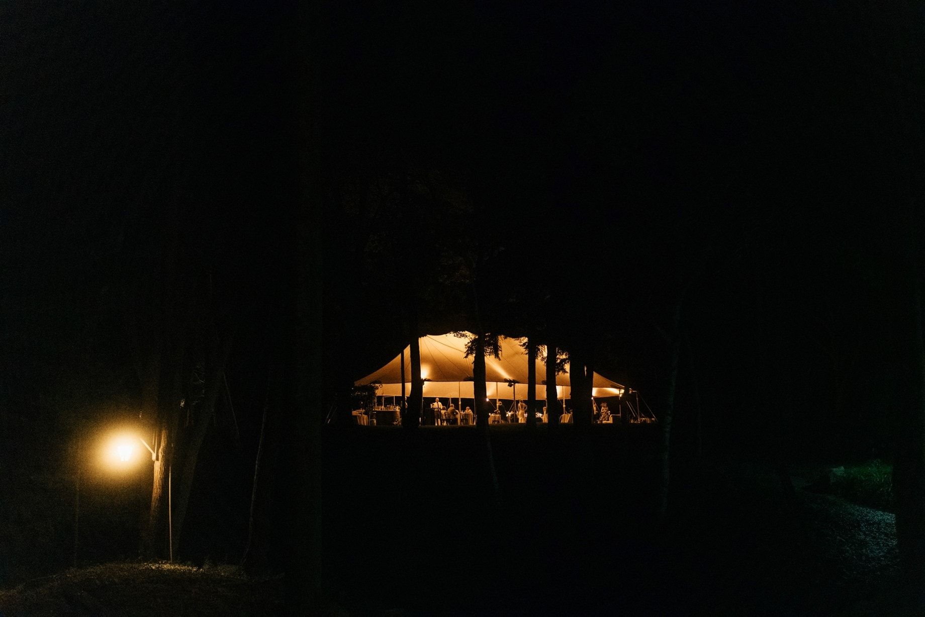 a night shot of a wedding reception tent in the woods